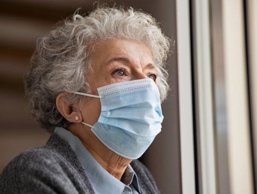 Sad senior woman wearing face protective mask at home