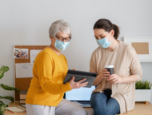 women in facemasks are using laptop